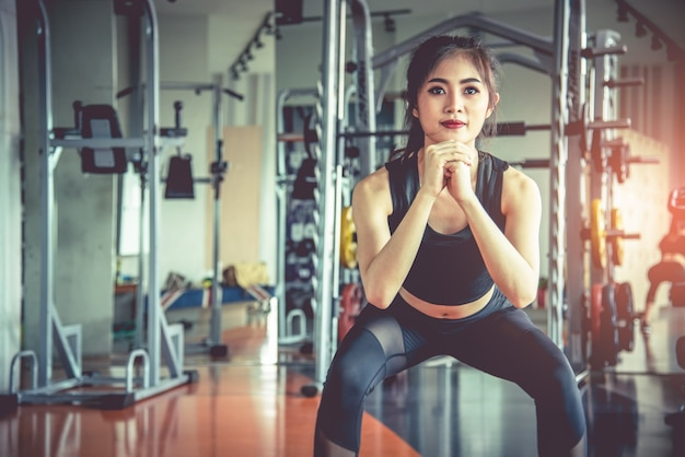 Jovem, mulher asiática, agarrando exercícios para queima de gordura e dieta no fitness sports gym