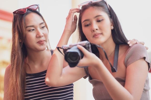 Jovem mulher asiática alegre e amiga na moda verão vestido sentado e olhando a foto depois de fotografar pela câmera no parque de diversões.