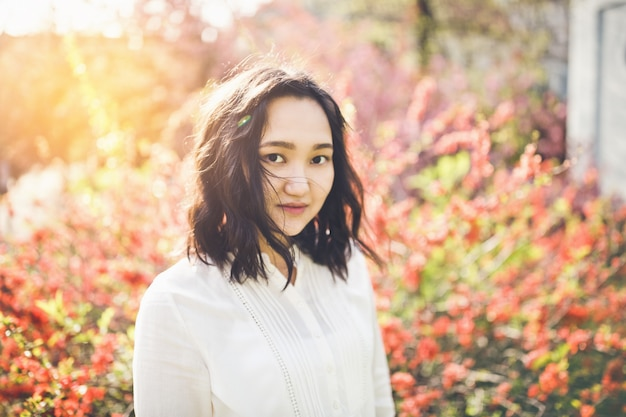 Jovem mulher asiática alegre em uma blusa branca em um parque de florescência.