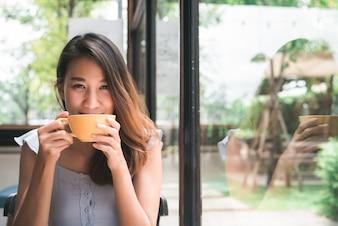 Jovem mulher asiática alegre que bebe o café ou o chá morno que aprecia a ao sentar-se no café