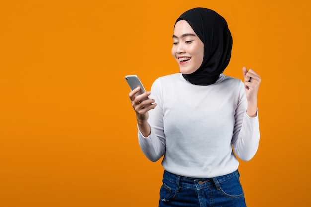 Jovem mulher asiática animada ao usar o telemóvel