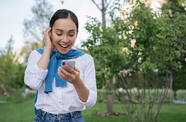 Jovem mulher asiática animada segurando um smartphone, usando um aplicativo móvel para fazer compras online