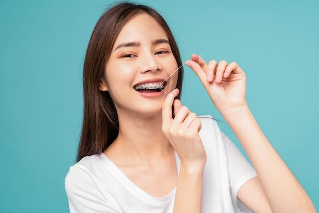 Jovem mulher asiática, aparelho de limpeza nos dentes com fio dental sobre fundo azul, conceito de higiene bucal e cuidados de saúde.