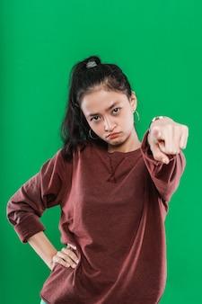 Jovem mulher asiática apontando para a câmera enquanto a expressão irritava o rosto em fundo verde