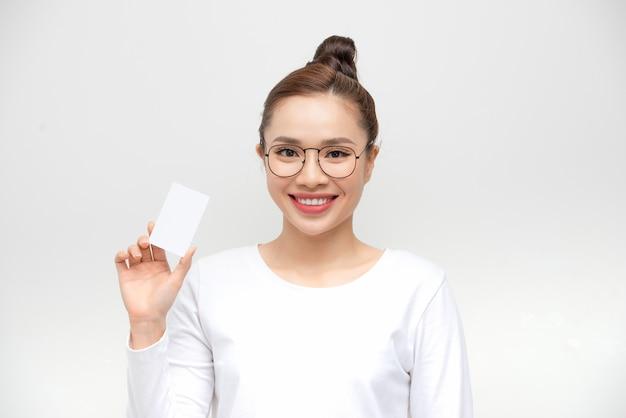 Jovem mulher asiática apontando para um cartão em branco na parede branca