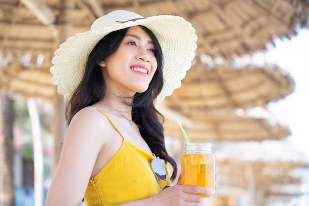 Jovem mulher asiática aproveitando as férias de verão na praia