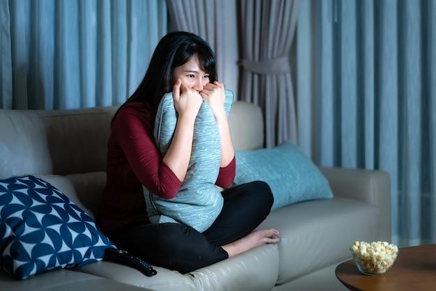 Jovem mulher asiática assistindo filme de suspense de televisão ou notícias olhando chocado e animado comendo pipoca tarde da noite em casa sofá da sala.