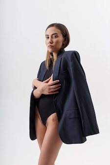 Jovem mulher asiática atraente em um body preto e um terno azul isolado no branco