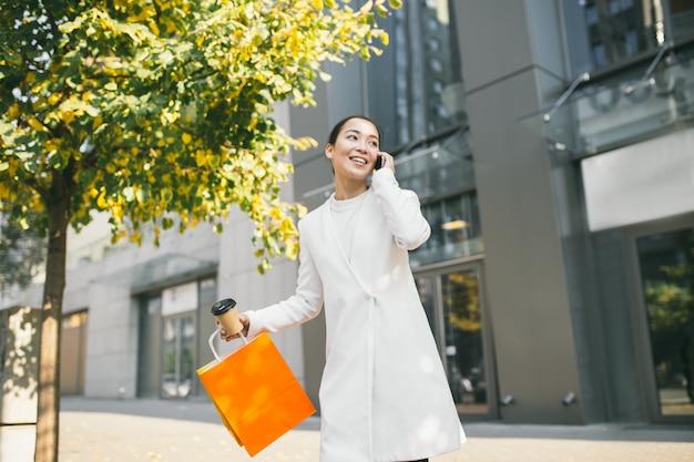 Jovem mulher asiática atraente está saindo de uma boutique de moda, falando no telefone e segurando café e sacolas de compras