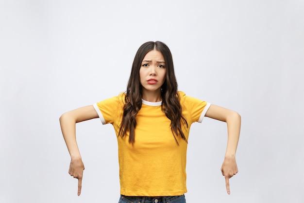 Jovem mulher asiática atraente que aponta para o dedo com emoção infeliz