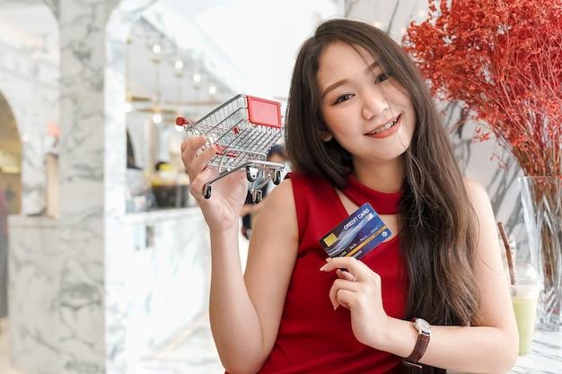 Jovem mulher asiática atraente sorrindo segurando o cartão de crédito e carrinho de compras enquanto relaxa no café