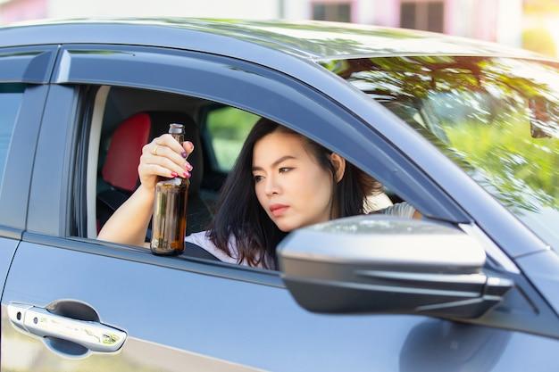 Jovem mulher asiática bebendo cerveja enquanto dirigia um carro