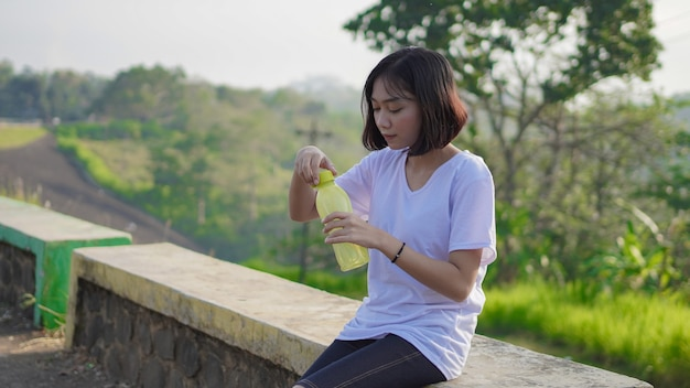 Jovem mulher asiática bebendo e descansando depois de correr pela manhã