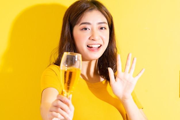 Jovem mulher asiática bebendo vinho e posando em amarelo