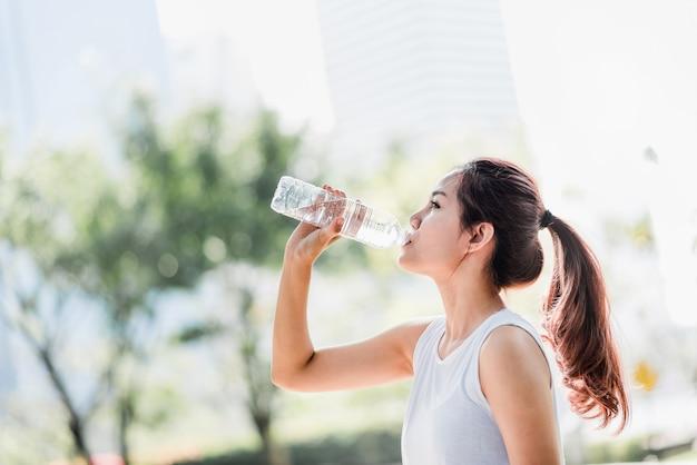 Jovem mulher asiática beber água de garrafa de água depois de correr no parque