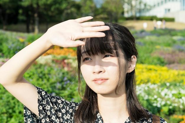 Jovem mulher asiática bloqueando a luz do sol com as mãos