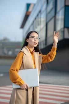 Jovem mulher asiática bonita acenando com a mão na estrada procurando um táxi Foto Premium
