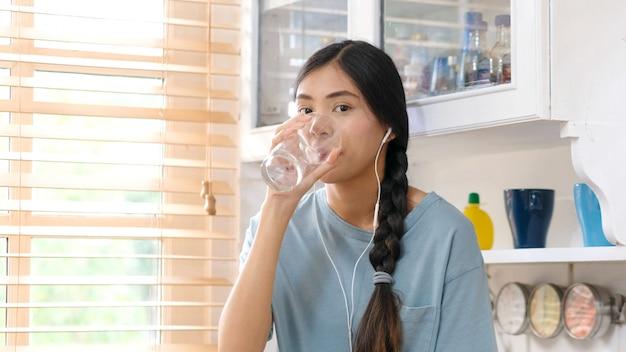 Jovem mulher asiática bonita água potável em pé pela janela na cozinha, pessoas e estilos de vida saudáveis
