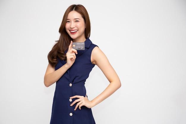 Jovem mulher asiática bonita apresentando cartão de crédito