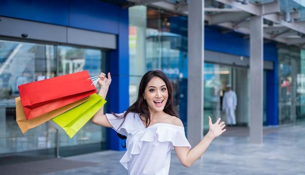 Jovem mulher asiática bonita com os sacos de compras com sorriso ao estar na loja de roupa. conceito de felicidade, consumismo, venda e pessoas