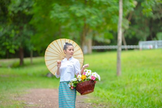 Jovem mulher asiática bonita do vestido tradicional norte de tailândia, cultura da identidade de tailândia.