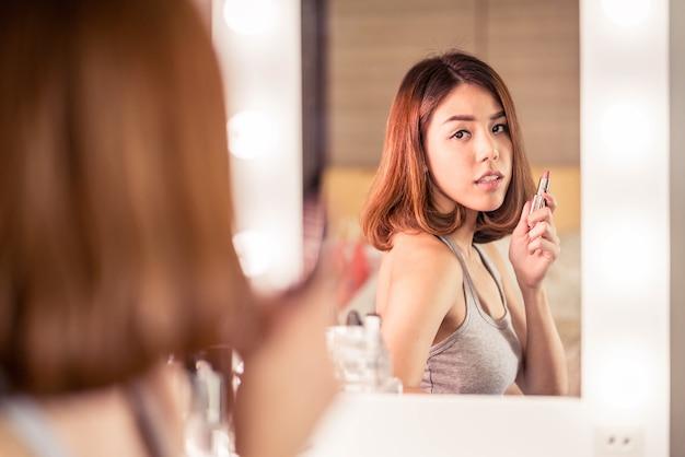 Jovem mulher asiática bonita fazendo maquiagem perto de espelho