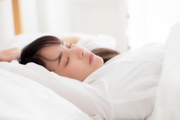 Jovem mulher asiática bonita que dorme deitado na cama com a cabeça no travesseiro confortável e feliz.