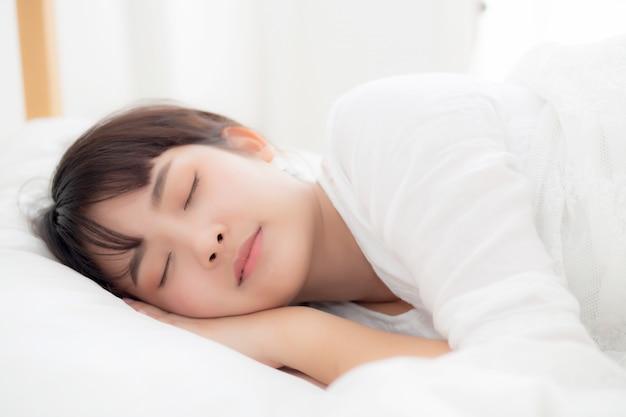 Jovem mulher asiática bonita que dorme encontrando-se na cama com cabeça no descanso confortável e feliz.