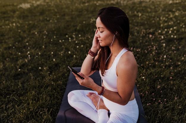 Jovem mulher asiática bonita relaxada após sua prática de ioga, ouvindo música em fones de ouvido e telefone celular.