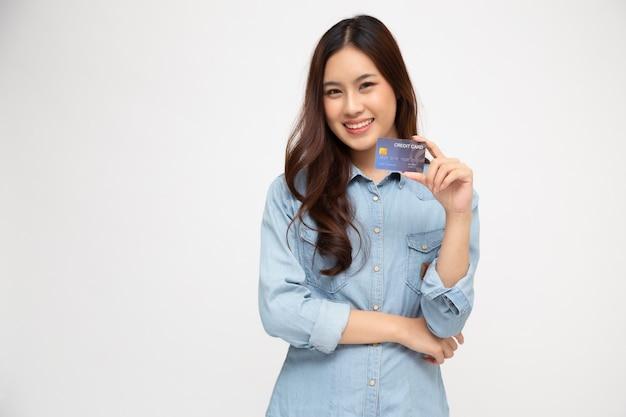Jovem mulher asiática bonita sorrindo, mostrando, apresentando cartão de crédito para fazer pagamentos ou pagar negócios on-line, pagar um comerciante ou como adiantamento em dinheiro para mercadorias, titular do cartão ou uma pessoa que possui um cartão Foto Premium