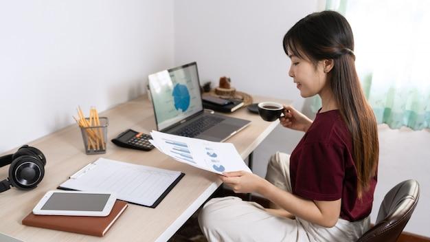 Jovem mulher asiática bonita trabalhando em casa