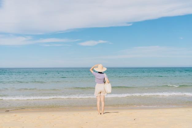 Jovem mulher asiática caminhando em uma praia tropical