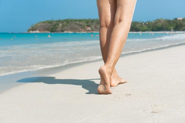 Jovem mulher asiática caminhando na praia de areia. conceito de viagens.