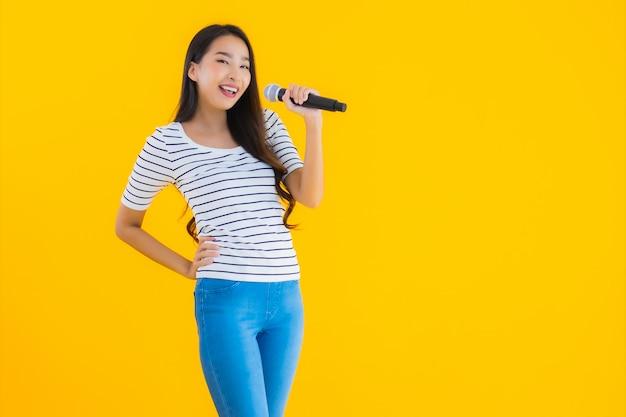 Jovem mulher asiática cantando com microfone