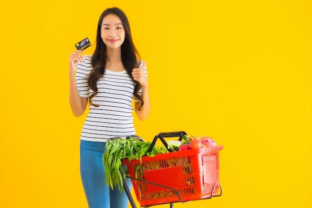 Jovem mulher asiática, carrinho de compras de supermercado