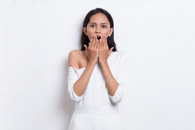 Jovem mulher asiática chocada cobrindo a boca com as mãos por engano. conceito secreto