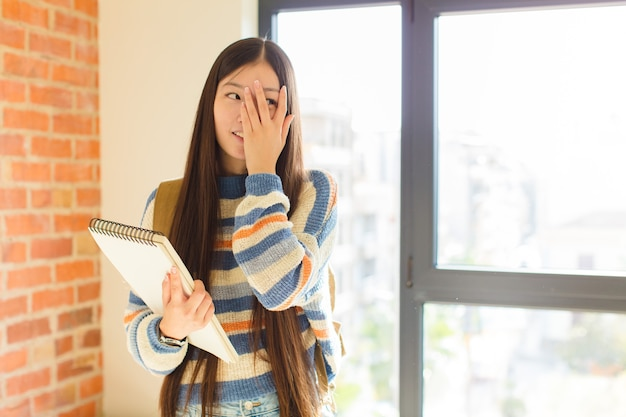 Jovem mulher asiática cobrindo o rosto com as mãos, espiando por entre os dedos com expressão de surpresa e olhando para o lado