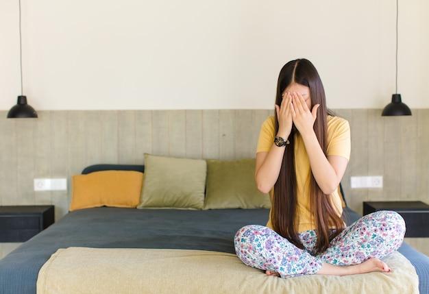 Jovem mulher asiática cobrindo os olhos com as mãos com uma expressão triste e frustrada de desespero, chorando, vista lateral