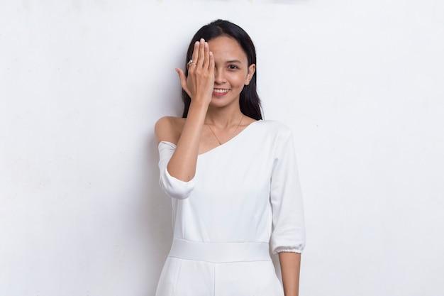 Jovem mulher asiática cobrindo um olho com a mão isolada no fundo branco