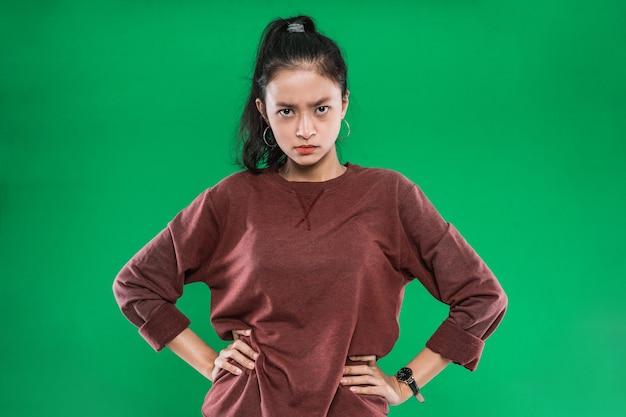 Jovem mulher asiática com as mãos na cintura enquanto a expressão irritava o rosto em fundo verde