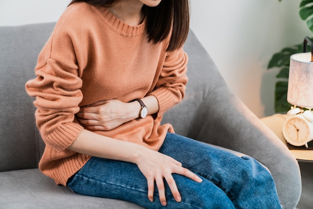 Jovem mulher asiática com as mãos segurando o estômago e cólicas menstruais.