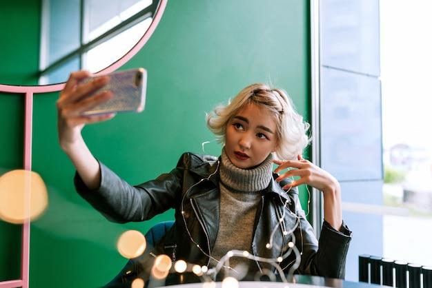 Jovem mulher asiática com cabelo loiro fazendo selfie com luzes de fada