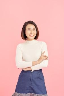 Jovem mulher asiática com camisola em pé sobre o rosto feliz de fundo rosa isolado, sorrindo com os braços cruzados, olhando para a câmera. pessoa positiva.