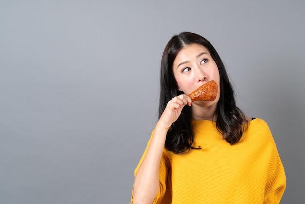 Jovem mulher asiática com cara feliz e gosta de comer coxinha de frango frito cinza