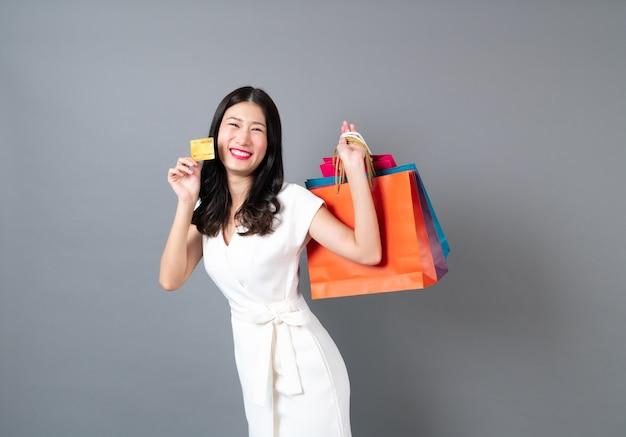 Jovem mulher asiática com cara feliz e mão segurando sacolas de compras e cartão de crédito na cinza