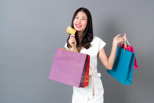 Jovem mulher asiática com cara feliz e mão segurando sacolas de compras e cartão de crédito