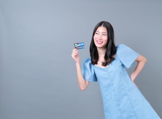 Jovem mulher asiática com cara feliz e mão segurando um cartão de crédito em um vestido azul