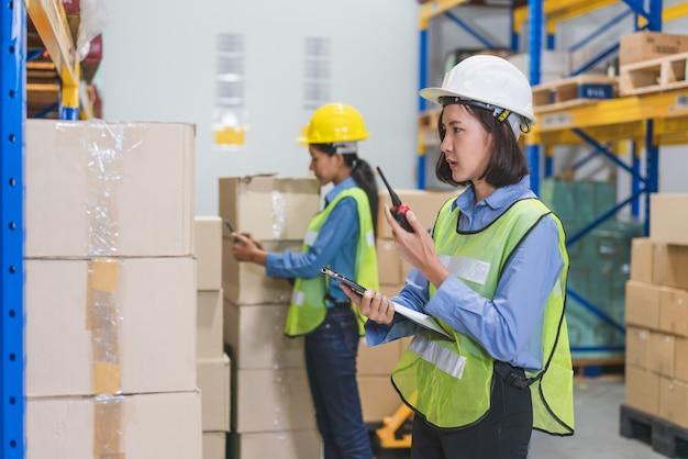 Jovem mulher asiática com colete de segurança e capacete amarelo, usando tablet, verificando produtos em estoque na fábrica do armazém