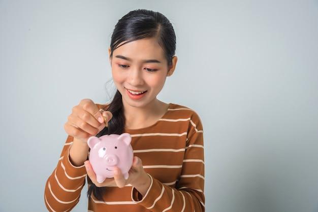 Jovem mulher asiática com dinheiro moeda e cofrinho