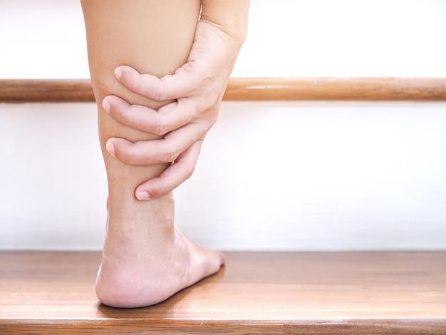 Jovem mulher asiática com dor no tornozelo e lesão na perna aguda ao subir escadas.